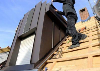 Dachdecker bei Spenglerarbeiten einer Dachgaube